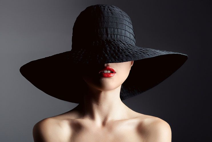 Chic young woman wearing red lipstick with face shielded by large brimmed black hat