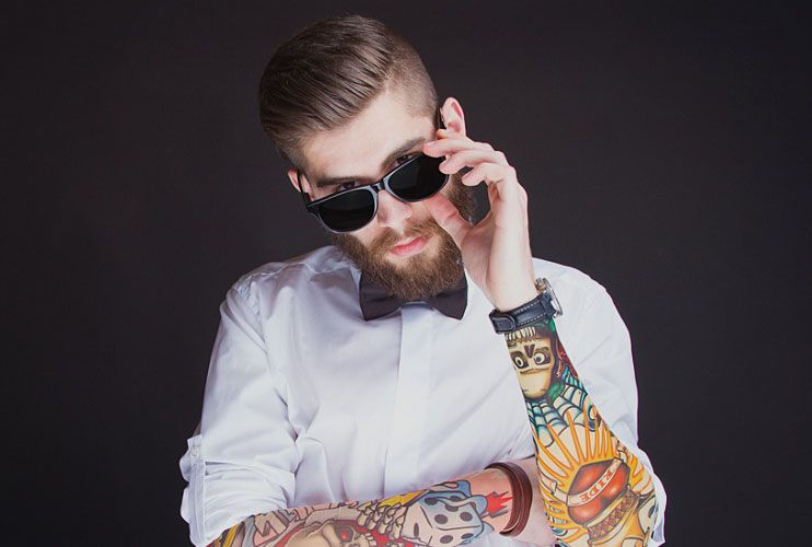 Young tattooed man in white shirt, looking over his sunglasses